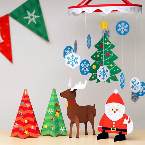A variety of homemade Christmas decorations including Santa, a reindeer, and a mobile with a twirling Christmas tree and snowflakes.