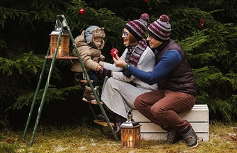 A family with a small child wear winter clothing in the garden.