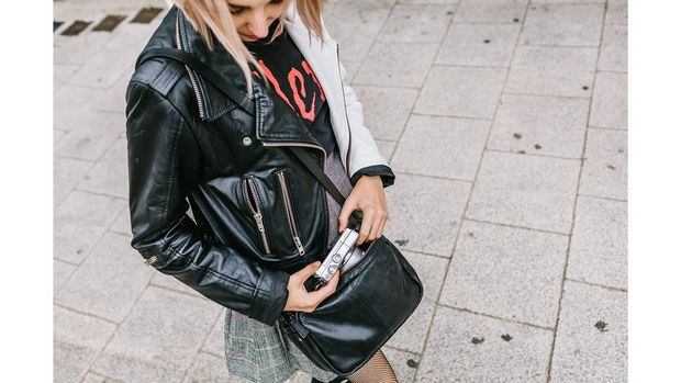 A girl wearing a leather jacket and skirt gets a compact camera out of her handbag.