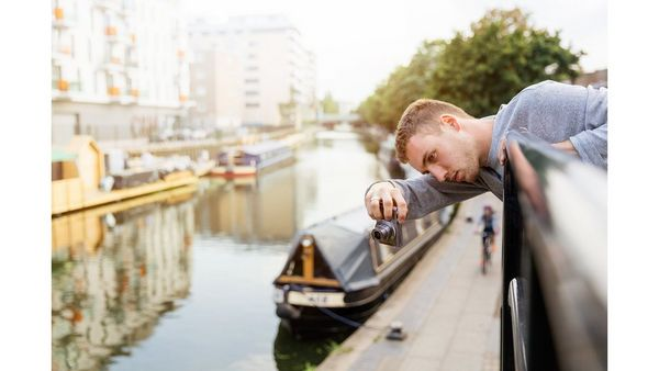 A man leans over some railings to take a picture. Below him is a canal with canal boats moored up.
