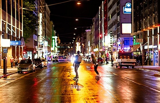 People skateboard down a city street at night.