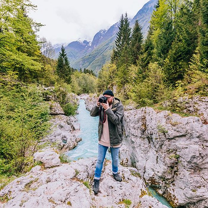 A man stands on rocks in front of a bright blue mountain river, taking a photo on a Canon camera.