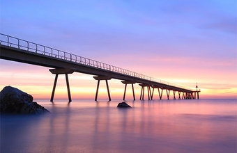 A wooden pier stretches over the sea at dawn.
