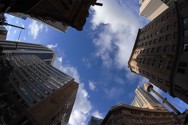 A view looking up at a blue sky, with tall buildings on all sides.