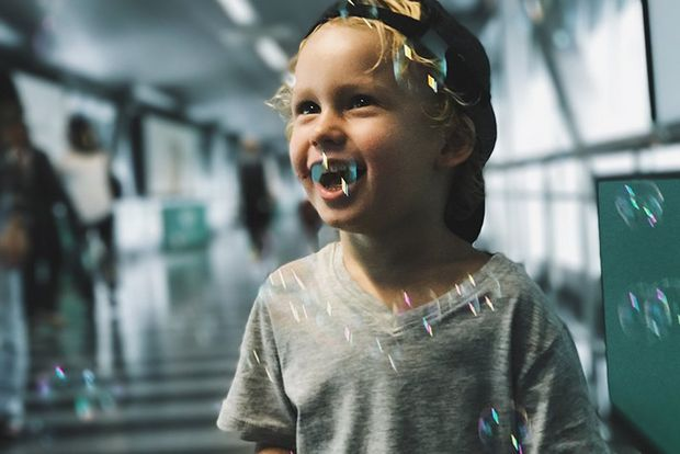 A boy smiles as bubbles float around him. Photo by Christian Anderl.