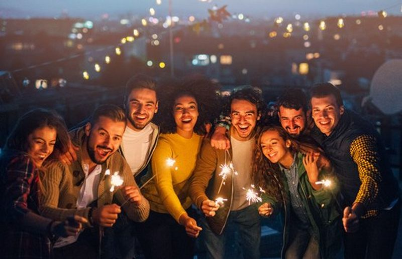 A group of friends at an outdoor party hold sparklers and smile.