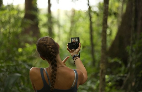 Laura Bingham pictured from behind, facing dense jungle, as she films a vlog with a Canon PowerShot G7 X Mark II.