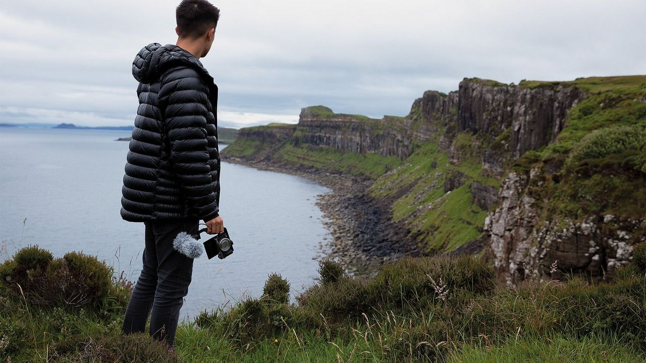 Mike Gray stands with his back to the camera looking at the Isle of Skye coastline, holding a Canon PowerShot G7 X Mark III with mic attached.