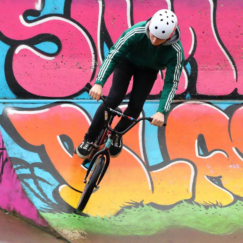 A BMX cyclist performs tricks on a bike ramp with bright graffiti on.