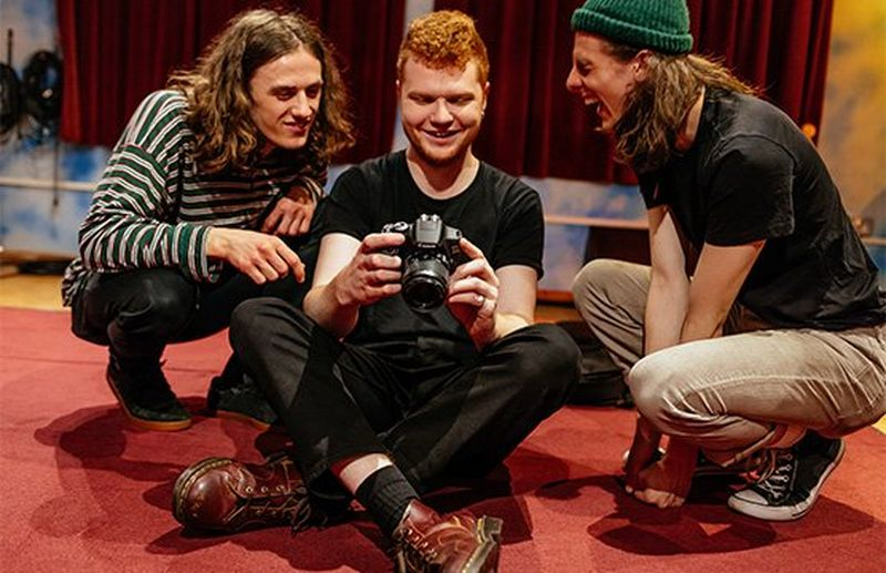 Music photographer Josh Gibbs holds a Canon EOS 2000D with two young men beside him.