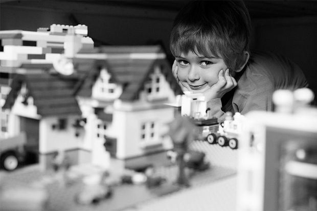A smiling boy with a Lego play set.