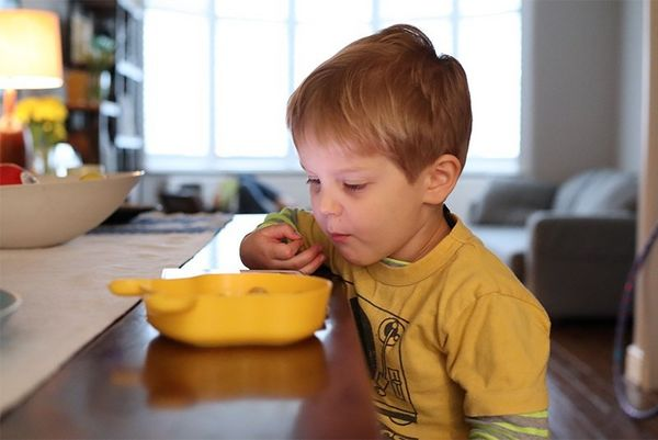 A boy looks into a yellow bowl on the table in front of him. Taken on a Canon EOS M50 by Katja Gaskell.