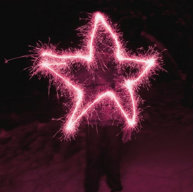 In a long-exposure image, a sillhouetted figure has drawn a bright pink five-pointed star with a sparkler.