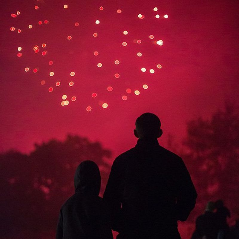 A firework turns the night sky red as it explodes. Below, trees and a crowd of people appear as silhouettes.