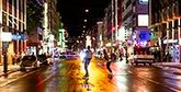 Two people skateboard down a city street at night, colourful lights from buildings reflecting in the wet road surface.