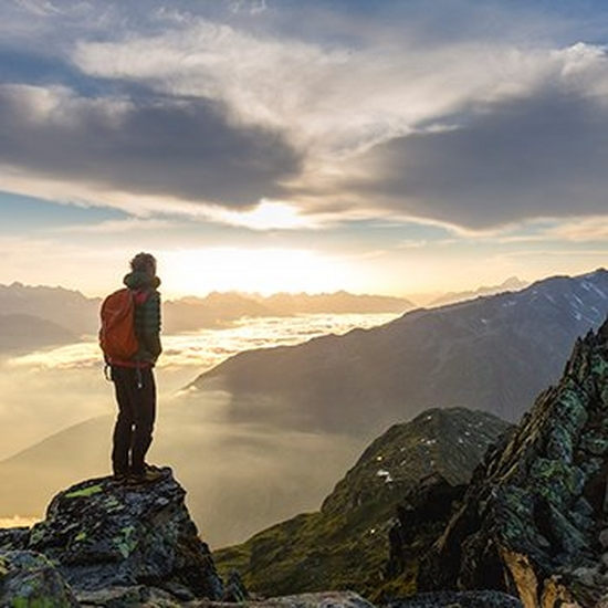 A hiker stands on top of a tall hill or mountain at dawn, arms outstretched.