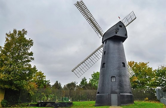 A windmill against a green countryside background on a cloudy day