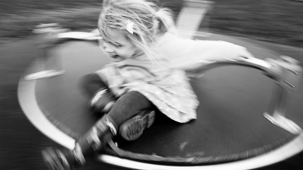 Motion-blur shot of a young girl playing on a roundabout.