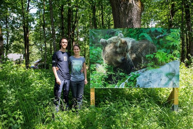 Christine and Marc stand by a printed version of one of their shots displayed as part of an outdoor exhibition in a forest.