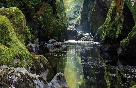 A narrow river or stream flanked by moss-covered rocks.