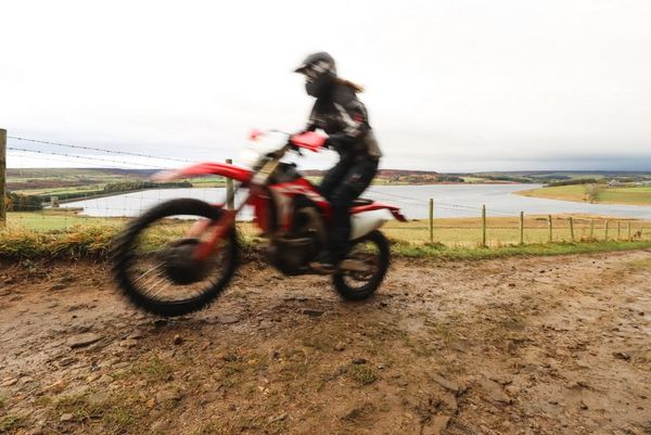 A blurred shot of a rider on a dirt-bike, the background in focus.