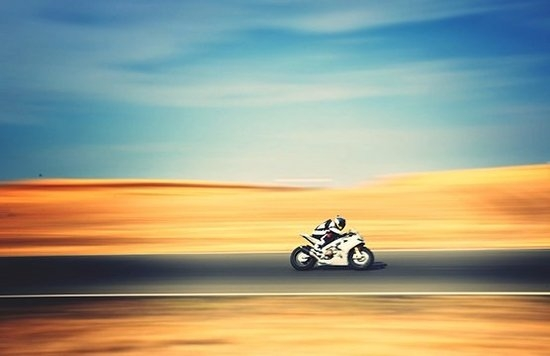 A motorbike streaks along a road, with the road and desert background a blur of colour.