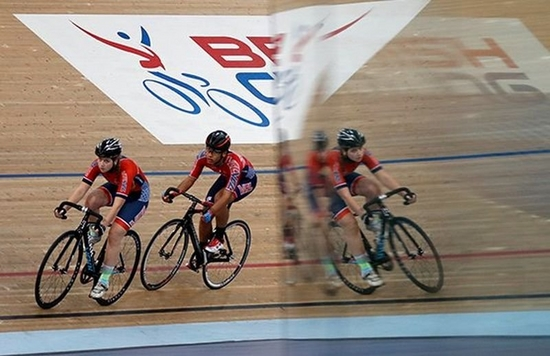 As two cyclists race along a velodrome track, they are reflected in a mirror-like surface. Photo by Eddie Keogh.