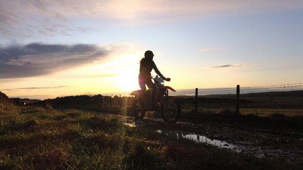 A woman on a dirt-bike is silhouetted against the setting sun.