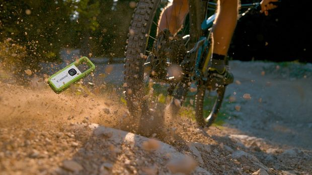 A green Canon IVY REC tumbles into the sand in the wake of a mountain bike.