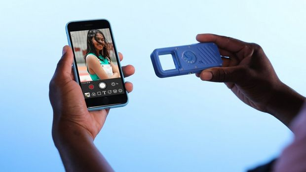 A blue Canon IVY REC being used with the Canon Mini Cam app on a smartphone, displaying a photo on its screen.