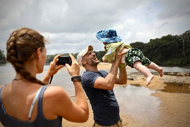 Laura photographs her husband Ed Stafford playing with their son on a beach.