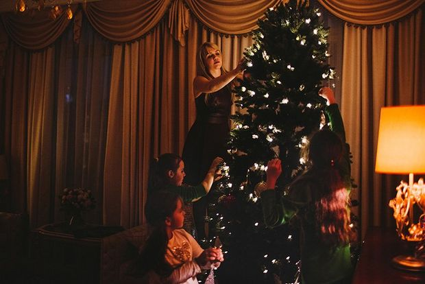 Three kids and their mother decorate a Christmas tree.