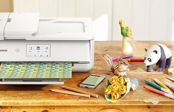 A Canon printer prints out patterned paper. A phone is next to the printer showing the same pattern.