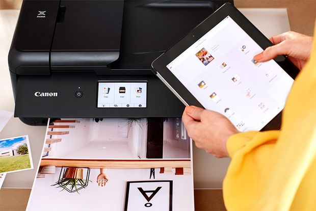 Woman standing next to a printer and operating it via her tablet.