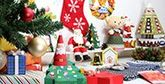 A table is filled with Christmas-themed paper crafted decorations and gifts.
