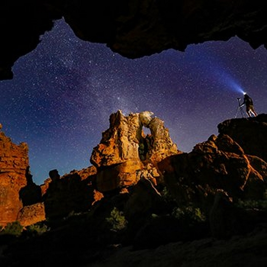 A photographer stands under the night sky in a desert wearing a head torch.