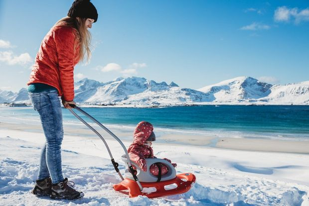 A woman pushes a child on a sled on the Lofoten Islands in Norway.