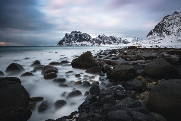 A long exposure shot of water surrounding rocks with a snowy mountain on the horizon.
