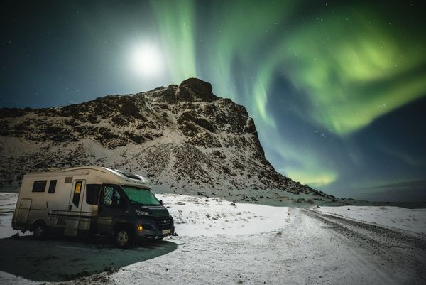 The Northern Lights swirl through the night sky above a mountain, with Markus Morawetz's campervan in the foreground.