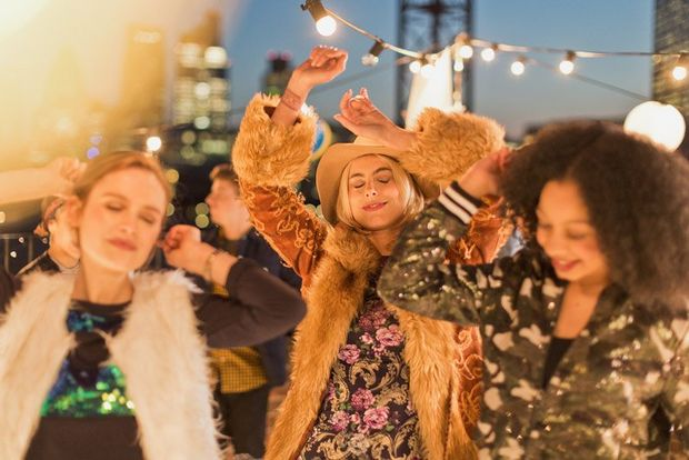 Three women are pictures dancing in a candid style, at a roof-top party.