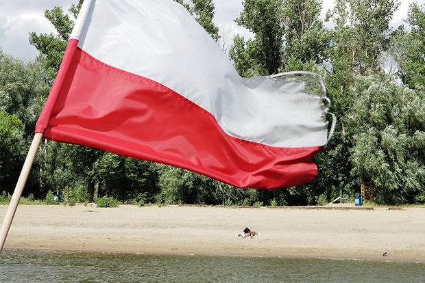 The Polish flag flutters in front of a beach, deserted but for one figure on the sand, with lush woods behind.
