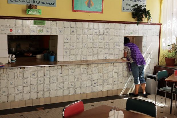 A woman leans through a hatch in a tiled wall in a cafe.