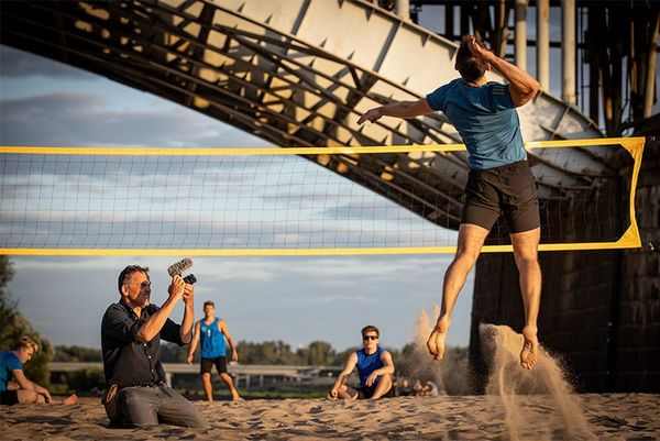 Photographer Piotr Malecki films a volleyball player on a sandy riverbank under a bridge.