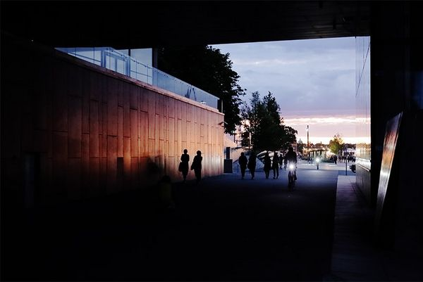 Pedestrians and bike riders on a wide walkway viewed from a dark underpass at sunset.