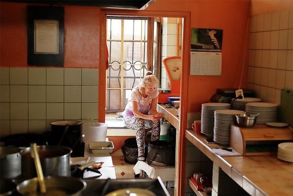 An older woman sits on a windowsill in a commercial kitchen.
