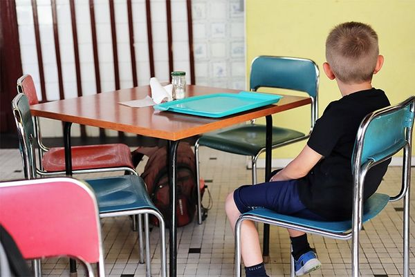 A young boy sits on one of several metal-framed chairs at a table in a cafeteria.