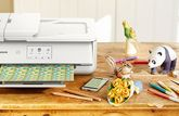 A Canon printer on a table with a papercraft panda and bouquet of flowers.