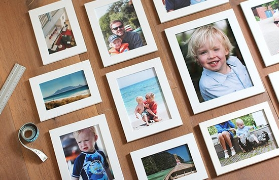 Printed photos in white frames laid out artistically.