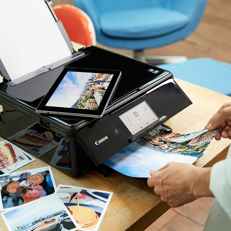 Hands taking prints from a Canon printer; a tablet on top showing a printing app.