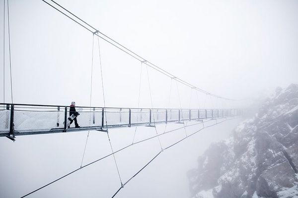 Olympic snowboarding champion Anna Gasser walking on a suspension bridge in fog.